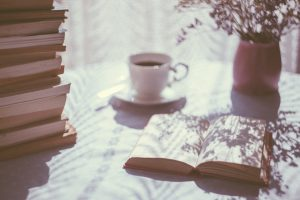 Bureau avec café plante et pile de livres