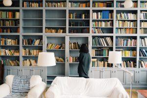 Femme devant une grande bibliothèque maison