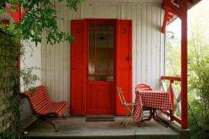 Entrée avec porte rouge et volets assortis, banc et table rouge à carreaux