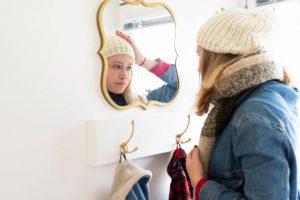 Jeune femme en train d'ajuster son bonnet dans le miroir de l'entrée