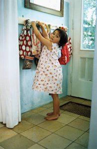Petite fille en train d'accrocher sa veste à une patère du hall d'entrée de sa maison