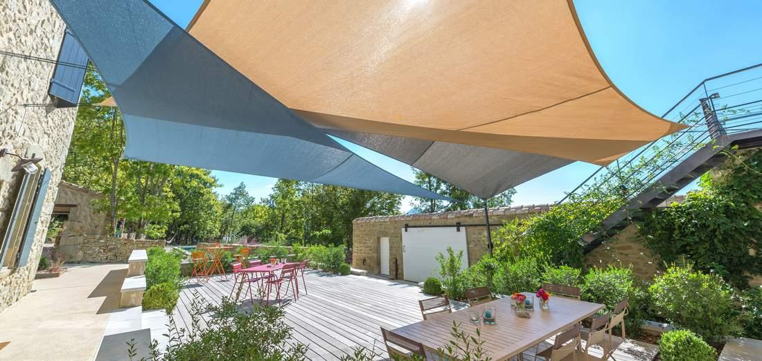 Superposition de voiles d'ombrage sur une terrasse ensoleillée
