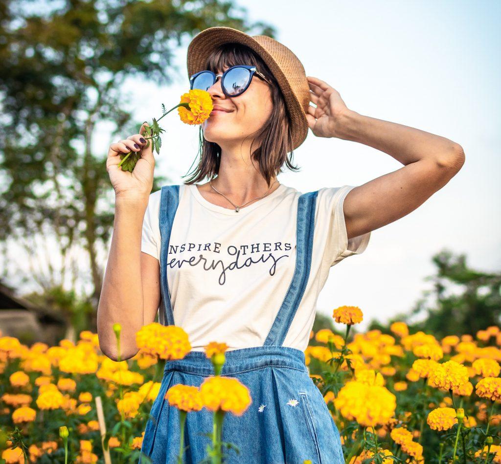 Jeune femme en traun de sentir le parfum d'une fleur jaune dans un champ