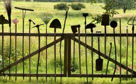 Accessoires pour le jardinage posés debout contre un portail en bois