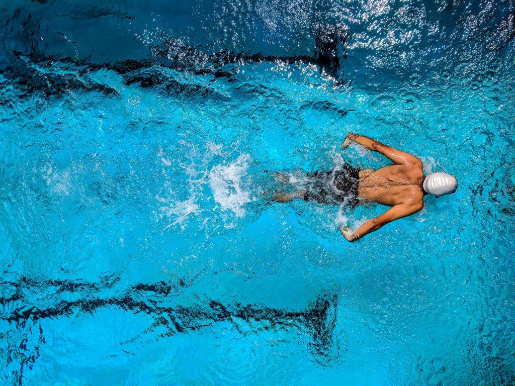 Homme qui pratique la nage sportive dans sa piscine