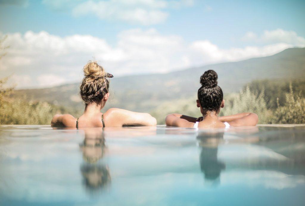 Deux jeunes femmes qui se prélassent dans l'eau chaude de leur piscine