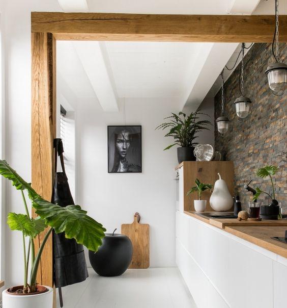 cuisine dans les tons blanc et bois avec un mur en pierres