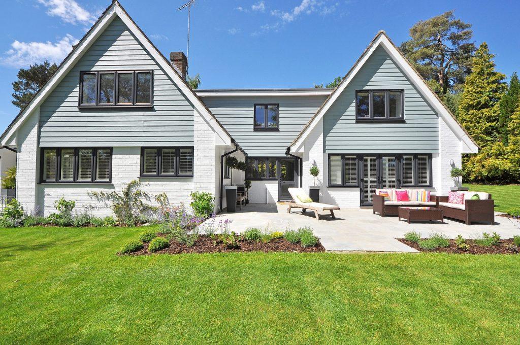 Grande maison avec terrasse bordée par une immense pelouse