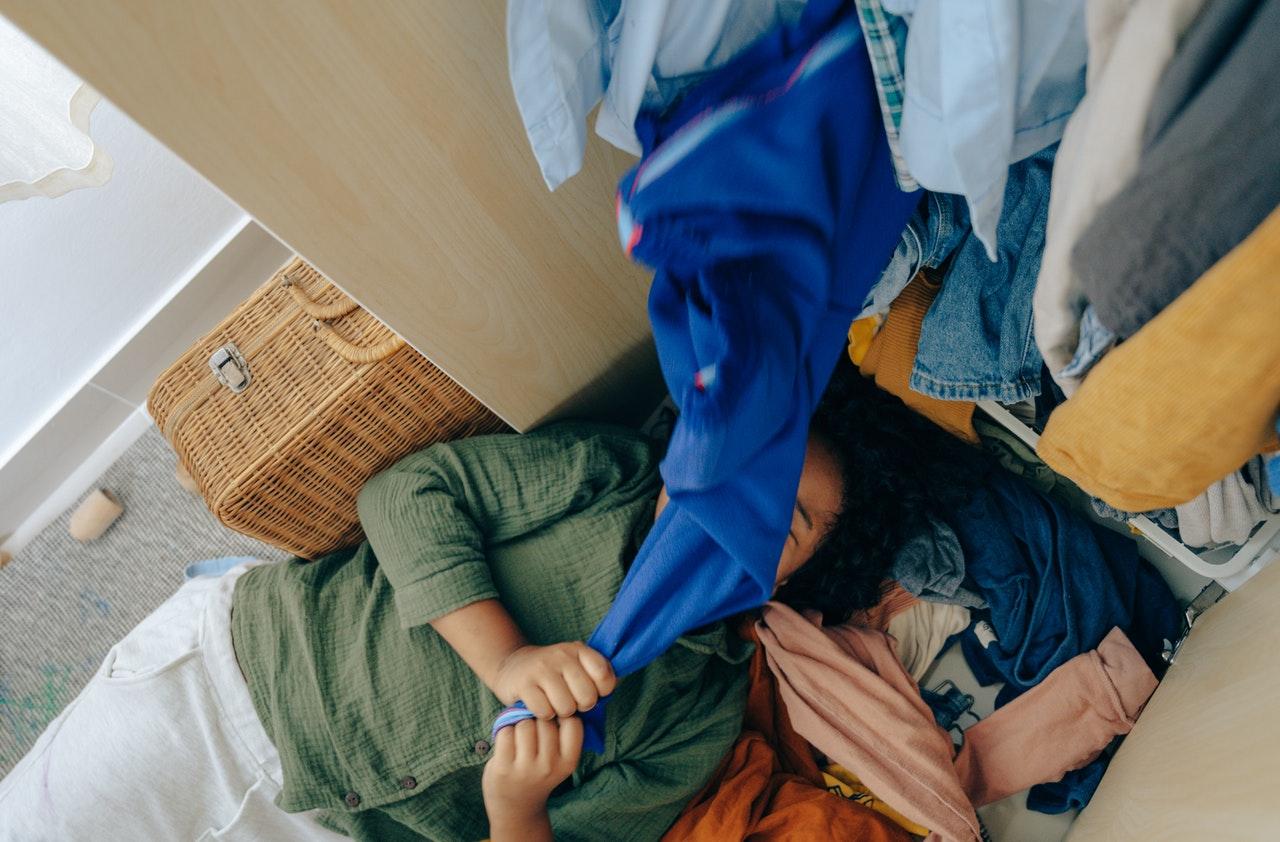 personne allongée sous des tas de vêtements